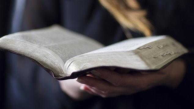 Woman holding bible (Stock photo)
