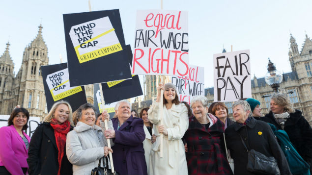 """Cast members of """"Made in Dagenham"""" protest with women from the original 1970 strike for equal pay. PHOTO: Vickie Flores/LNP/REX/Shutterstock"""
